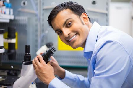Portret close-up, jonge vriendelijke wetenschapper op zoek naar microscoop. Geïsoleerde lab achtergrond. Sector onderzoek en ontwikkeling