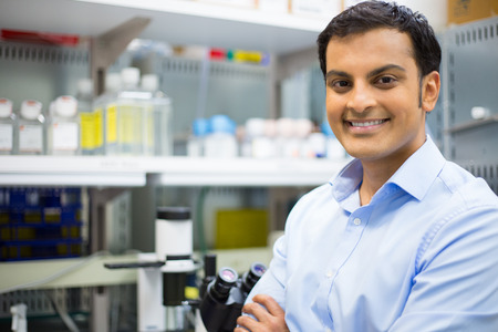 Closeup portrait, young friendly scientist standing by microscope. Isolated lab background. Research and development sector