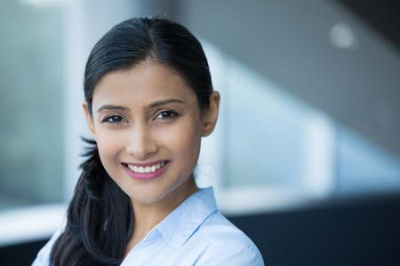 Detailansicht-Porträt, junge professionelle, schöne selbstbewusste Frau im blauen Hemd, freundliche Persönlichkeit, lächelnd in Innenräumen Bürohintergrund. Positive menschlichen Emotionen