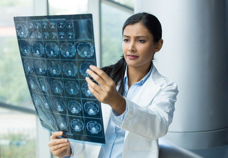 asian doctor: Closeup portrait of intellectual woman healthcare personnel with white labcoat, looking at full body x-ray radiographic image, ct scan, mri, isolated hospital clinic background. Radiology department