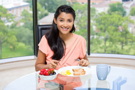 Closeup portrait of a young, attractive businesswoman, kick start day with healthy breakfast, fruit bowl, egg ,green tea, smiling energetic employee. Isolated glass window indoor greenery background. photo