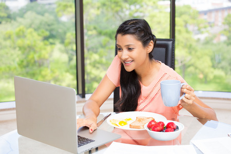 Closeup portrait, young, attractive businesswoman, kick start day with healthy breakfast, smiling on laptop. Isolated glass window indoor green trees background. The early bird catches the worm.