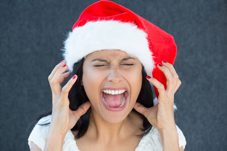 Closeup portrait of a cute Christmas woman with a red Santa Claus hat, white dress, screaming out loud, frustrated, eyes shut in rage. Negative human emotion on an isolated grey background. photo