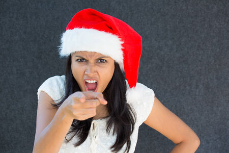christmas debt: Closeup portrait, cute Christmas woman with a red Santa Claus hat, white dress, pointing at camera, is that you expression, negative human emotion, isolated grey background. Whos naughty or nice?