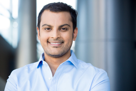 Closeup headshot portrait, happy handsome business man, smiling, in blue shirt,confident and friendly on isolated office interior background. Corporate success photo