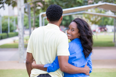 Closeup portrait of a young couple holding, embracing each other, expression of love, happy moments, positive human emotions on isolated outdoors park background. Women in blue shirt looking back photo