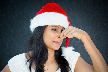 Closeup portrait of pretty young woman in santa claus hat closing covering nose, something stinks, isolated gray black background. Negative facial expressions, emotions, feelings,