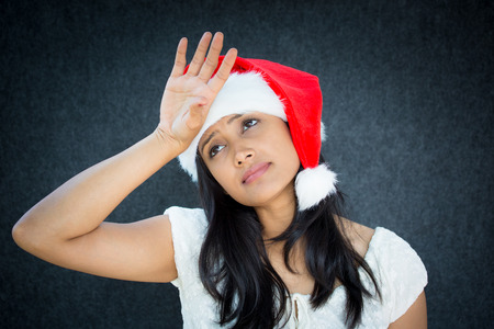christmas debt: Closeup portrait of annoyed woman in Santa Claus hat, hand on forehead playing tragedy, expressing holiday stress, isolated on grey background. Negative human emotions, facial expressions, attitude
