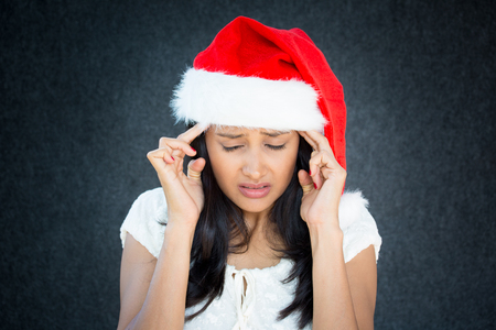 last minute: Closeup portrait, young beautiful worried stressed wife, mother, woman in santa claus hat with hands on temples looking down, isolated gray black background. Last minute christmas shopping Stock Photo