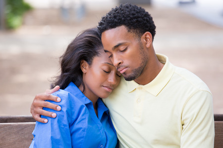 Closeup portrait of a young couple holding, embracing each other, eyes closed sleeping, expression of love, happy moments, positive human emotions on isolated outdoors park bench background. Stockfoto