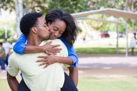 若いカップルのクローズ アップの肖像画、男女性ピギーバックの乗車を与えるおよび肯定的な人間の感情、幸せな瞬間の顔にキスを孤立屋外外パー