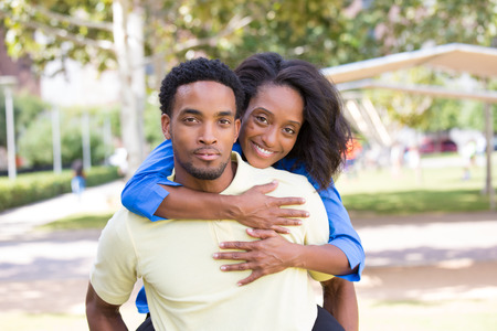 Closeup portrait of a young couple,guy giving woman piggy back ride, happy moments, positive human emotions on isolated outdoors outside park background. photo