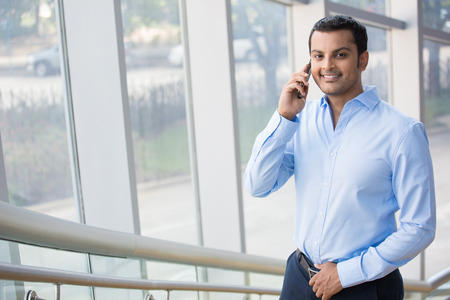 A closeup portrait of a young busy, happy, smiling business man talking on his phone while walking on the office building staircase, isolated on indoor glass window background. Corporate success