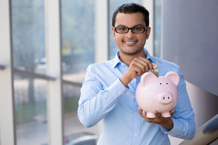 putting in: Closeup portrait, young business man in blue shirt, black glasses, putting money in piggy bank, isolated indoor glass background, management and savings concept