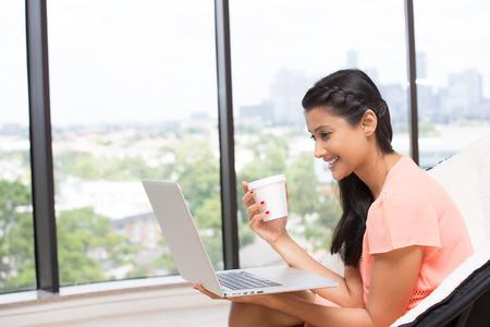 cafe colombiano: Primer retrato, joven, atractiva esposa, madre, con la taza blanca, sonriendo mirando portátil. Ventana de cristal aislado interior fondo de árboles verdes. mujer en un mundo de tecnología concepto Foto de archivo