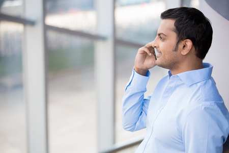 man looking out: A closeup portrait of a young busy, happy, smiling business man in blue shirt, talking on his phone, looking out of the window, isolated on indoor glass window office background. Corporate success Stock Photo