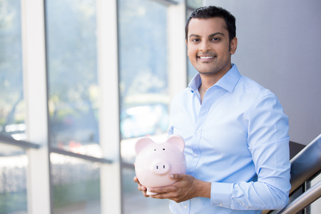 mutual funds: Closeup portrait happy, smiling businessman, holding pink piggy bank, isolated indoors office background. Financial budget savings, smart investment concept Stock Photo
