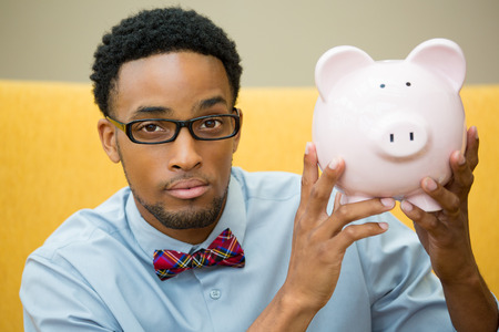 education loan: Closeup portrait happy, smiling businessman in black glasses and bowtie, holding pink piggy bank, isolated indoors office background. Financial budget savings, smart investment concept