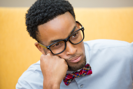 Closeup portrait, young disturbed, distressed computer geek with big black glasses, bow tie, and blue shirt, hand on cheek worried about something.