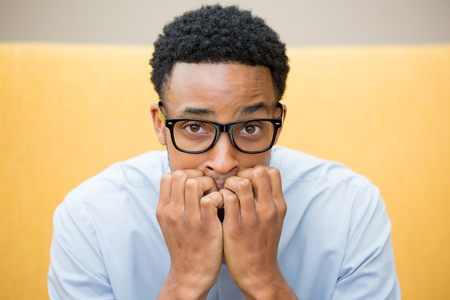 Closeup portrait of young nerdy unhappy guy with big black glasses and blue shirt, wide open eyes, biting his nails and looking to camera with a craving for something or anxious, worried.