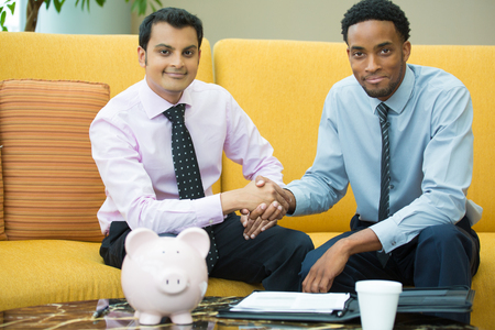 lawyer meeting: Closeup portrait, two young men in ties shaking hands, isolated yellow couch background with piggy bank and coffee on table foreground