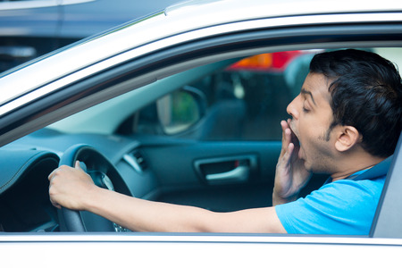 long hours: Closeup portrait tired young funny man in blue shirt with short attention span, driving his black car after long hours trip, yawning at wheel, isolated outside background. Sleep deprivation