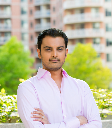 Closeup portrait, happy handsome, confident businessman in pink shirt, arms folded, crossed,  outside of his office during sunny day, isolated city urban balcony background. Corporate success Archivio Fotografico