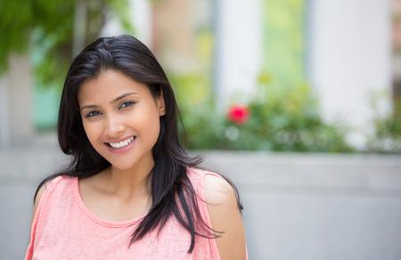 carita feliz: Retrato del primer de confianza sonriendo feliz mujer joven y bonita en vestido de color rosa, fondo aislado de �rboles borrosas, flores. Emoci�n positiva humana sentimientos de expresi�n facial, la actitud, la percepci�n Foto de archivo