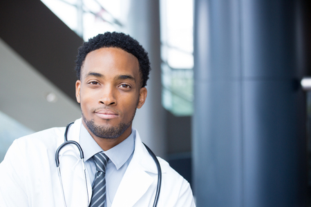 Closeup portrait head shot of friendly, smiling confident male doctor, healthcare professional with a white coat and stethoscope, looking at the camera, isolated hospital clinic background.