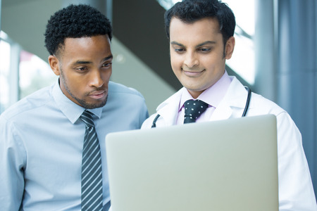 findings: Closeup portrait of intellectual healthcare professional with white labcoat, looking at patient record, discussing findings with patient, using digital technology, isolated hospital clinic background