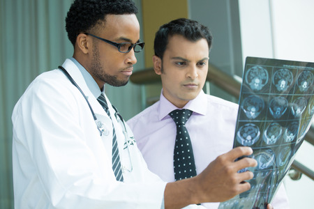 doc: Closeup portrait of intellectual healthcare professionals with white labcoat, looking at full body x-ray radiographic image, ct scan, mri, isolated hospital clinic background. Radiology department