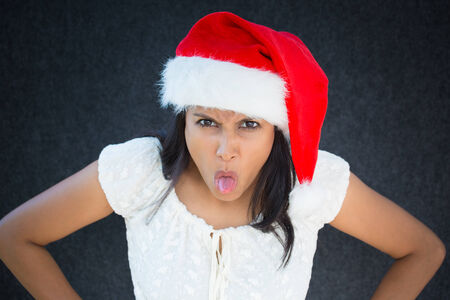 disrespectful: Closeup portrait of unhappy, pissed off christmas woman, with red hat,sticking tongue out, disgusted, negative human facial expression, isolated on grey black background. Emotions, signs, symbols