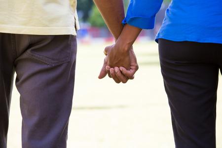romantik: Närbild porträtt av ett ungt par med kemi, håller varandra i handen, lyckliga stunder, engagemang, kärlek och romantik koncept, positiva mänskliga känslor på isolerade utomhus utanför park bakgrund.