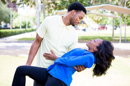 Closeup portrait of a young couple, guy holding woman in arms in dip, looking at each other, dance pose, love and romance concept, positive human emotions on isolated outdoors outside park background.