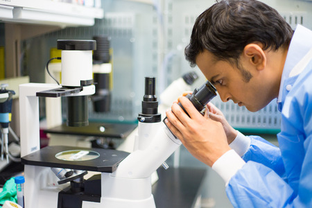 clinical: Closeup portrait, young scientist in blue gown looking into microscope. Isolated lab background. Research and development.