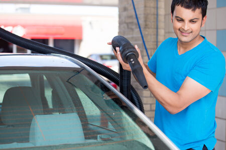 intact: Closeup portrait, young man driver in blue shirt, air drying his silver car with vacuum hose after washing. Safe for expensive paint and chrome. A touch less process that keeps the wax intact Stock Photo