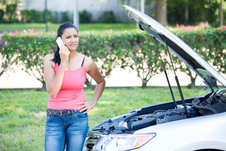 Closeup portrait, young woman in pink tanktop having trouble with her broken car, opening hood and calling for help on cell phone, isolated green trees and shrubs outside background