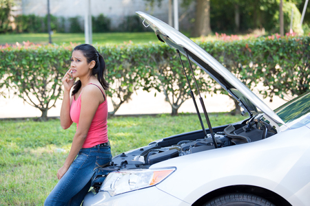 car trouble: Closeup portrait, young woman in pink tanktop having trouble with her broken car, opening hood and calling for help on cell phone, isolated green trees and shrubs outside background