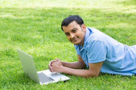 person outdoors: Closeup portrait, young brown man in blue polo shirt lying on grass, working on his silver personal laptop computer. Surfing the world wide web net, leisure learning