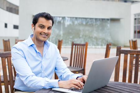Closeup portrait, happy young handsome man in blue shirt typing away, browsing digital computer laptop, isolated background of sunny outdoor, waterfall, brown chairs, office background photo