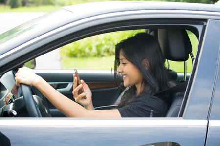 Closeup portrait, young woman with good news, happily texting on cellphone while driving, isolated outside background. Banco de Imagens