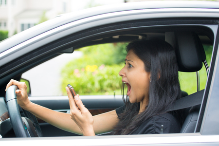 Closeup portrait, young woman driving in black car and checking her phone, then shocked almost about ot have traffic accident, isolated outdoors background