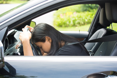 Closeup portrait tired young attractive woman with short attention span, driving her car after long hours trip, trying to stay awake at wheel, isolated outside background. Sleep deprivation