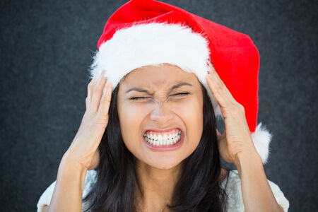 forgot: Closeup portrait, young beautiful worried stressed wife, mother, woman in santa claus hat with hands on temples about to break down, isolated gray black background. Last minute christmas shopping