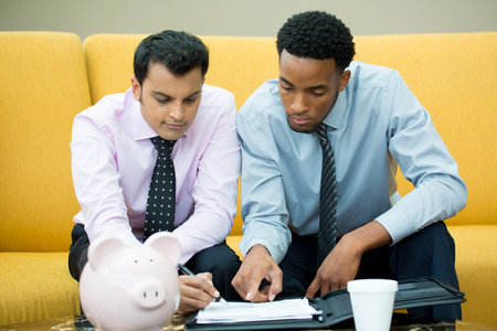 lawyer meeting: Closeup portrait, two young men in ties doing paper work for a contract isolated yellow couch background with piggy bank and coffee on table foreground