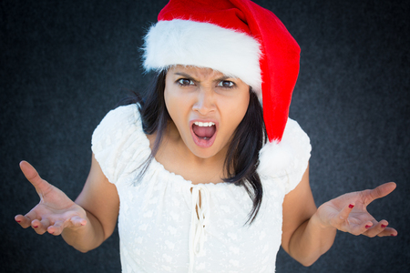 Closeup portrait, unhappy, young, pretty woman in red santa claus hat, white dress, asking why, how could you do this. Isolated gray black background. Negative human emotions