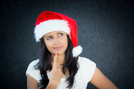 Closeup portrait of a cute christmas woman with a red santa claus hat, white dress, finger on chin, confused, thinking what to shop for the holiday season. Emotion on isolated grey background. photo