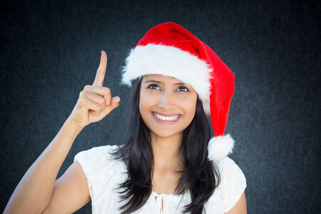 aha: Closeup portrait of happy christmas woman, with red hat, pointing with index finger, aha i have an idea, positive human facial expression, isolated on grey black background. Emotions, signs, symbols Stock Photo