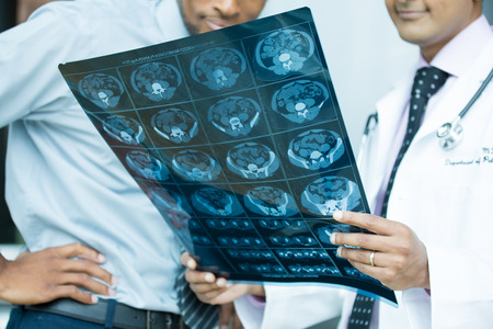 Closeup portrait of intellectual healthcare professionals with white labcoat, looking at full body x-ray radiographic image, ct scan, mri, isolated hospital clinic background. Radiology department