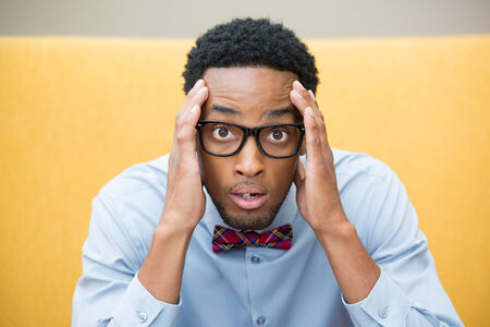 socially: Closeup portrait, stunned nerd young man, hands on head, open mouth jaw drop with bow tie and big glasses, isolated yellow background. Negative human emotion facial expression feelings